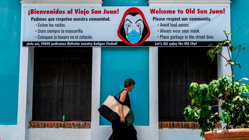 A woman walks pass by a banner urging visitors to wear face masks in San Juan, Puerto Rico