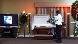 Joseph Louis pays his respects to German Amaya, who he worked with for 10 years, as family and friends held a wake ceremony at the Maspons Funeral Home in Miami, Florida