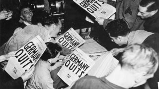 Allied soldiers and others read copies of the Stars and Stripes military newspaper, off the press (belonging to the London Times), that announces Germany's surrender in World War II, London, England, May 7, 1945.