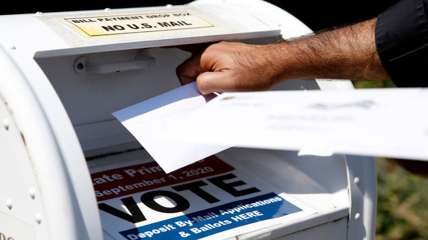 A voter drops a ballot into the box for mail-in ballots