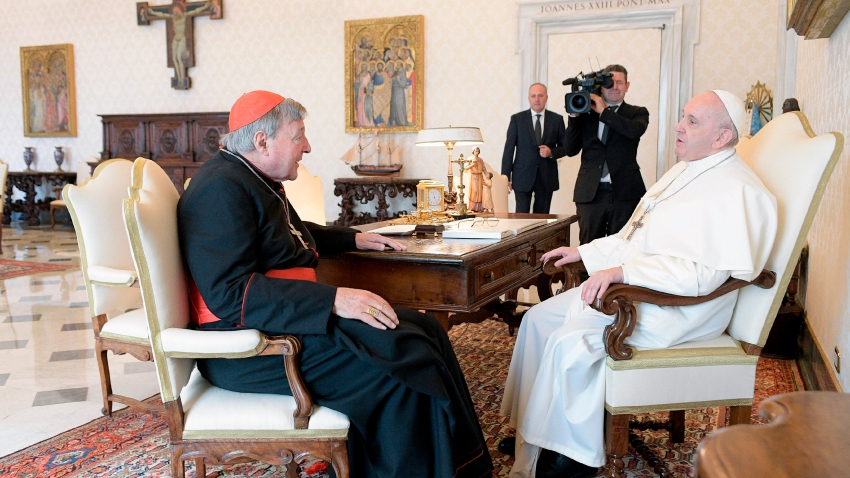 Pope Francis, right, sits at a table with Cardinal George Pell