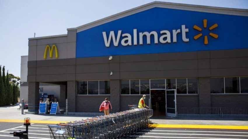 In this July 16, 2020, file photo, an employee wearing a protective mask pulls carts towards a Walmart store in Lakewood, California.