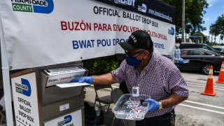 In this Aug. 18, 2020, file photo, poll workers help a voter put their mail-in ballot in an official Miami-Dade County drive-thru ballot drop box during Florida Primary Election amid the coronavirus pandemic, in Miami, Florida.