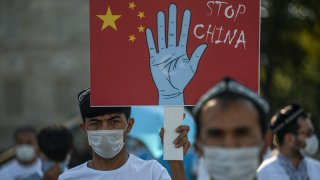 Supporters of China's Muslim Uyghur minority wave flags of East Turkestan and hold placards as they gather at the Beyazid square on October 1, 2020 during a demonstration to protest China's Uighur treatment in Istanbul.