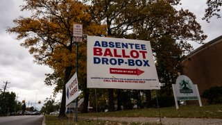 In this Oct. 15, 2020, file photo, a sign directs voters to the absentee ballot drop-box in Detroit, Michigan.