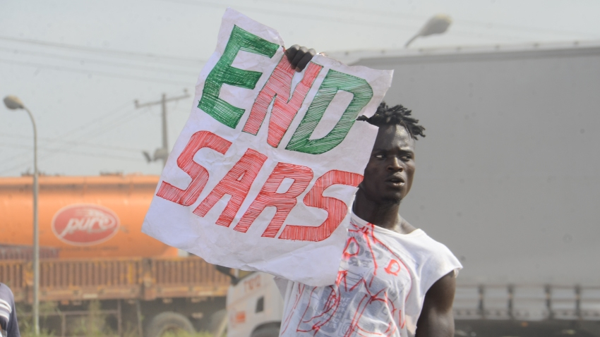 "A protester holds a sign reading ""End SARS"""