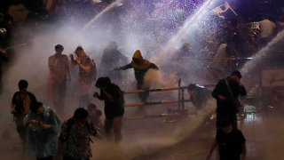 Police use water canons to try and disperse demonstrators from their protest venue in Bangkok, Thailand, Oct. 16, 2020.