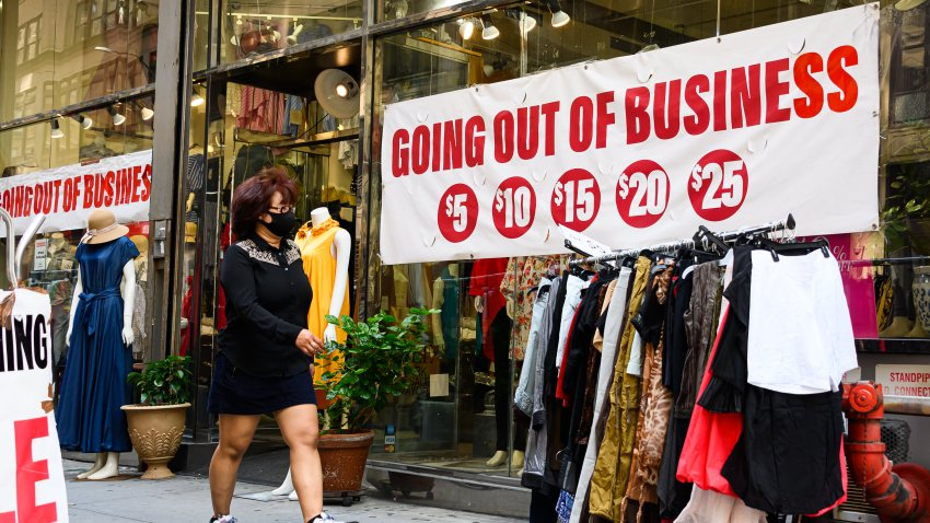 A pedestrian wearing a protective face mask walks by a going out of business sign displayed outside a retail store