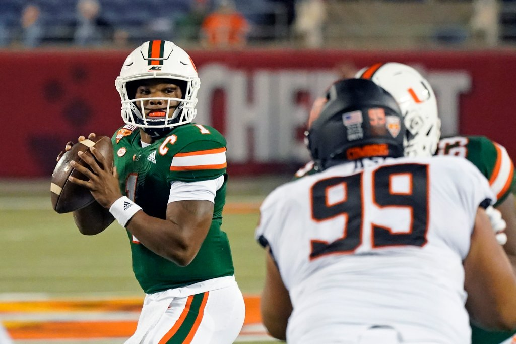 Miami quarterback D'Eriq King looks for a receiver as Oklahoma State defensive tackle Sione Asi rushes during the first half of the Cheez-it Bowl