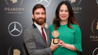 Andy Mills and Rukmini Callimachi pose with the Peabody award