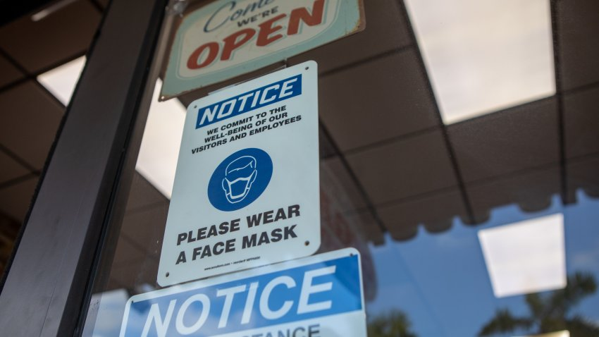 Social-distancing and mask wearing signs on a storefront during the 2020 Presidential election in Miami, Florida, U.S., on Wednesday, Nov. 4, 2020.