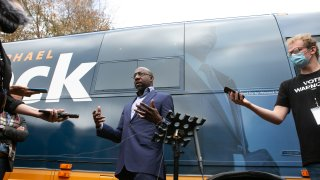 Democratic U.S. Senate candidate Raphael Warnock talks with the press outside his campaign bus during a drive-up worship service at St. James Missionary Baptist Church on December 13, 2020 in Columbus, Georgia. Warnock is facing incumbent Sen. Kelly Loeffler (R-GA) in a runoff election that will take place on January 5th. The results of two Georgia U.S. Senate races will determine which party controls the Senate.