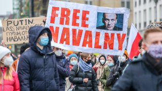 "In this Jan. 23, 2021, file photo, protesters hold a banner reading ""FREE NAVALNY"" as some 2,500 supporters of Russian opposition politician Alexei Navalny march in protest to demand his release from prison in Moscow in Berlin, Germany."