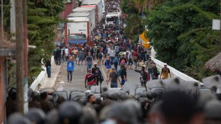 Honduran migrants, top, stand next to cargo trucks as they confront Guatemalan soldiers and police