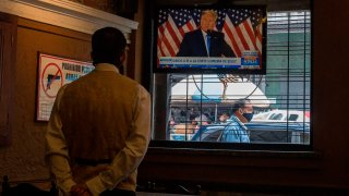 US President Donald Trump is displayed on a television screen at a restaurant in Caracas, Venezuela, on November 4, 2020, amid the COVID-19 coronavirus pandemic.