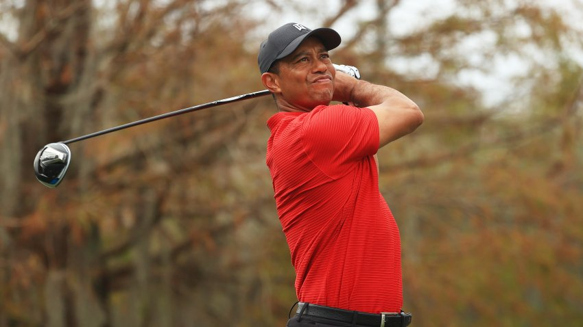 In this Dec. 20, 2020, file photo, Tiger Woods of the United States plays his shot from the ninth tee during the final round of the PNC Championship at the Ritz-Carlton Golf Club Orlando in Orlando, Florida.