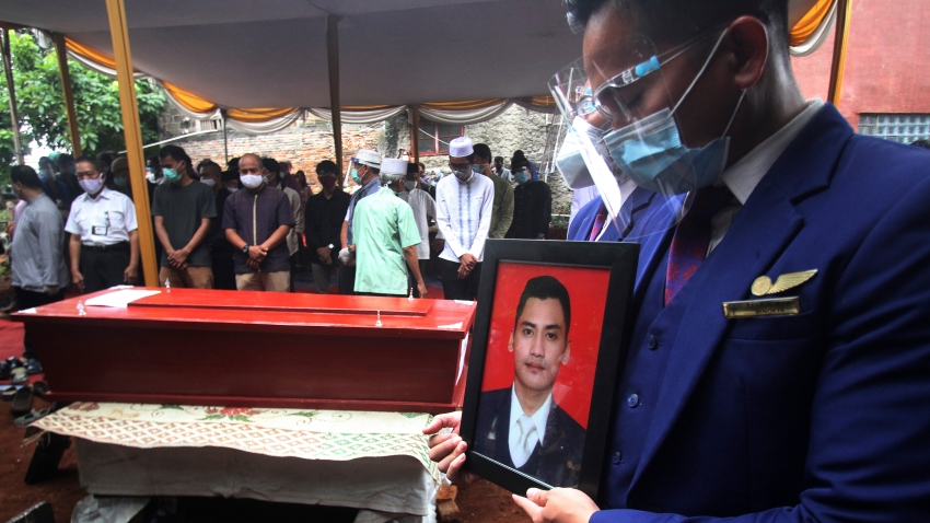 A colleague holds a portrait of Okky Bisma, a flight steward, one of victims of the crashed Sriwijaya Air passenger jet during his funeral in Jakarta, Indonesia.Thursday, Jan. 14, 2021. An aerial search for victims and wreckage of the crashed Indonesian plane expanded Thursday as divers continued combing the debris-littered seabed looking for the cockpit voice recorder from the lost Sriwijaya Air jet.