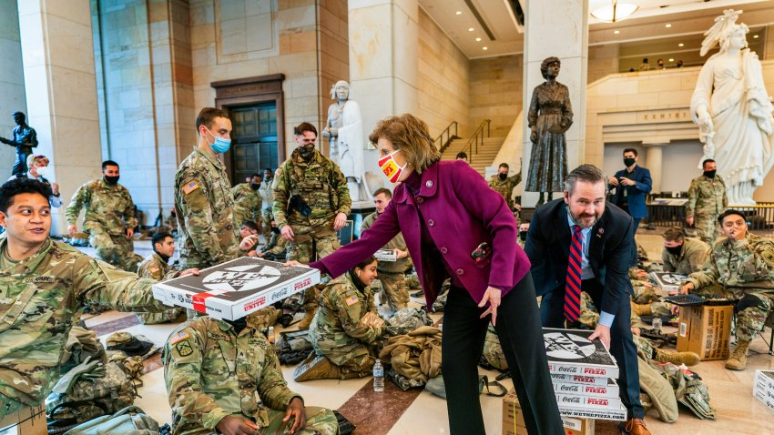 Rep. Vicky Hartzler, R-Mo., and Rep. Michael Waltz, R-Fla., hand pizzas to members of the National Guard gathered at the Capitol Visitor Center, Wednesday, Jan. 13, 2021, in Washington, D.C., as the House of Representatives continues with its fast-moving House vote to impeach President Donald Trump, a week after a mob of Trump supporters stormed the U.S. Capitol.
