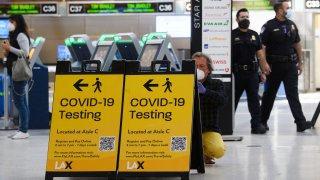 In this Feb. 4, 2021, file photo, a traveler takes a photo of a COVID-19 testing sign at the Tom Bradley International Terminal (TBIT) amidst travel restrictions during the COVID-19 pandemic at Los Angeles International Airport (LAX) in Los Angeles, California.