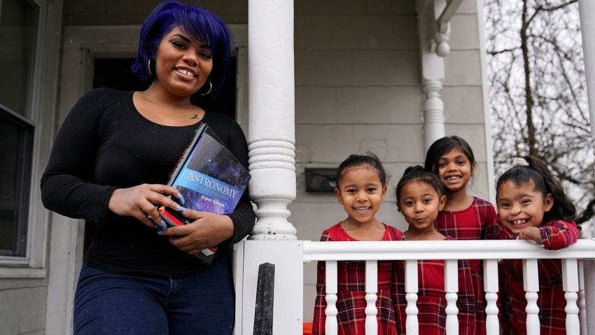Dinora Torres, a MassBay Community College student, poses with her four daughters on the front porch of their home