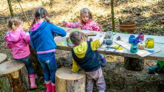 Kindergarten kids having fun drawing and creating on a wooden table in nature.