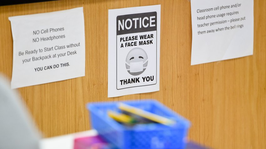 """West Lawn, PA - October 22: A sign in a classroom that reads """"Notice, please wear a face mask. Thank you"""" next to signs about rules of cell phone usage in class. At Wilson High School in West Lawn, PA Thursday afternoon October 22, 2020 where the school has been taking precautions for students doing in person school to prevent the spread of Coronavirus / COVID-19."""