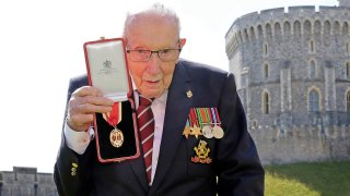 FILE - In this July 17, 2020 file photo, Captain Sir Thomas Moore poses for the media after receiving his knighthood from Britain's Queen Elizabeth, during a ceremony at Windsor Castle in Windsor, England.