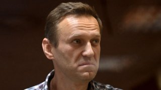 In this Feb. 20, 2021, file photo, Russian opposition leader Alexei Navalny stands inside a glass cell during a court hearing at the Babushkinsky district court in Moscow.