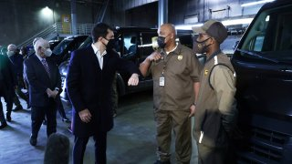 U.S. Secretary of Transportation Pete Buttigieg (L) greets United Parcel Service (UPS) employee Joe Jackson (2nd R) with an elbow bump during a tour at a UPS facility that is delivering vaccines to Washington, DC, and Maryland areas March 15, 2021 in Landover, Maryland.