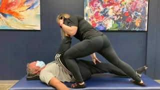 Tara Albarron, 32, works with client Ron Bryant, 55, of Beaver Creek, Ohio, during an assisted stretching session at StretchLab in Centerville, Ohio, on March 8, 2021. Assisted stretching is intended to improve range of motion, flexibility and circulation, among other benefits.