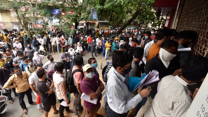 People wait in queues outside the office of the Chemists Association to demand necessary supply of the anti-viral drug Remdesivir, in Pune, India