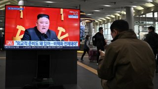 People watch a television screen at Suseo railway station in Seoul on March 26, 2021, showing file footage of North Korea's leader Kim Jong Un as a news programme reports about the North's latest tactical guided projectile test.