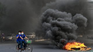 This picture taken on April 3, 2021 shows people cycling past a burning makeshift barricade, erected by protesters demonstrating against the military coup, in Yangon's Tamwe township, Myanmar.