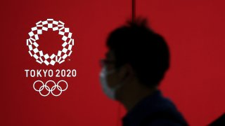 A pedestrian walks past a Tokyo 2020 Olympic Games logo on a decoration board in Tokyo on April 7, 2021.