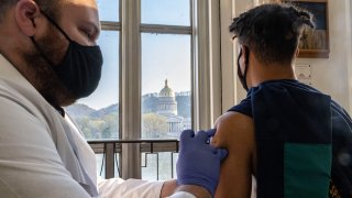 Antonio Sneed, 19, of Morgantown, West Virginia receives the vaccine while overlooking the West Virginia Capitol Building in Riggleman Hall. The Kanawha-Charleston Health Department led a vaccination effort on the campus of the University of Charleston. 1,800 doses of the Johnson & Johnson Janssen Covid-19 vaccine were on hand to be given out to all persons aged 16 years and older.