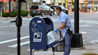 A United States Postal Service (USPS) worker wearing a protective mask and gloves makes his rounds in the Chelsea neighborhood of Manhattan as the city continues Phase 4 of re-opening following restrictions imposed to slow the spread of coronavirus on August 20, 2020 in New York City.