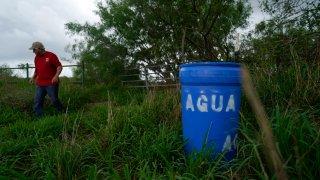 Eduardo Canales walks behind one of his blue water drops