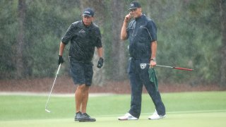 Phil Mickelson and NFL player Tom Brady of the Tampa Bay Buccaneers stand in the rain on the 13th green during The Match: Champions For Charity at Medalist Golf Club on May 24, 2020 in Hobe Sound, Florida.