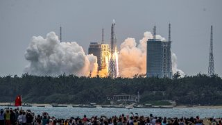 People watch a Long March 5B rocket, carrying China's Tianhe space station core module, as it lifts off from the Wenchang Space Launch Center in southern China's Hainan province on April 29, 2021.