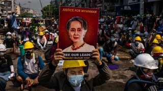 An anti-coup protester holds up a placard featuring de-facto leader Aung San Suu Kyi on March 02, 2021 in Yangon, Myanmar.
