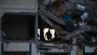 Palestinians search for survivors under the rubble of a destroyed rooftop of a residential building which was hit by Israeli missile strikes, at the Shati refugee camp in Gaza City, early Tuesday, May. 11, 2021.