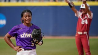 James Madison starting pitcher Odicci Alexander (3) stands in the pitching circle as Oklahoma's Jayda Coleman (24) celebrates at second base behind her