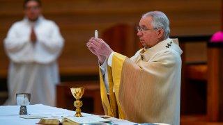 Archbishop Jose H. Gomez holds a Communion wafer
