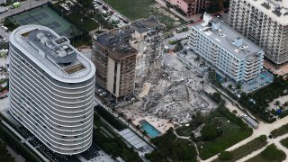 In this aerial view, search and rescue personnel work after the partial collapse of the 12-story Champlain Towers South condo building on June 24, 2021 in Surfside, Florida.