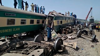 Soldiers and volunteers work at the site of a train collision in Ghotki district in southern Pakistan, Monday, June 7, 2021. Two express trains collided in southern Pakistan early Monday, killing dozens of passengers, authorities said, as rescuers and villagers worked to pull injured people and more bodies from the wreckage.