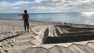Sand sculptors adorns the beach beside the area that is closed for search and rescue operations at the partially collapsed Champlain Towers South condo building