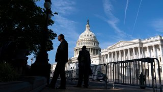 The U.S. Capitol is seen as people walking on the sidewalk with a fence, in Washington