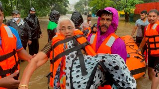 A National Disaster Response Force personnel carries an elderly woman through water.