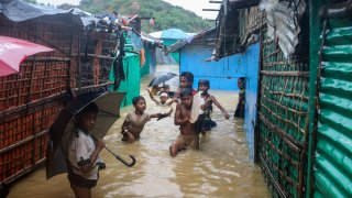 Rohingya refugee children play in flood waters at the Rohingya refugee cam