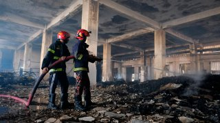 Firefighters work to douse a fire at a food and beverage factory in Rupganj, outside Dhaka, Bangladesh, Friday, July 9, 2021. At least 52 people died in a huge blaze that engulfed a food and beverage factory outside Bangladesh's capital, fire officials said Friday, in the latest industrial disaster to hit the South Asian nation.